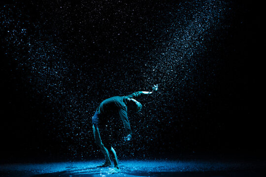 Ballet dancer against the background of falling snow and studio light. A man posing on a black background.
