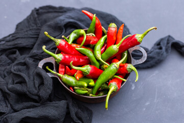 Top view of the green and red hot chili peppers in a rusty cup with cloth on a dark tabletop
