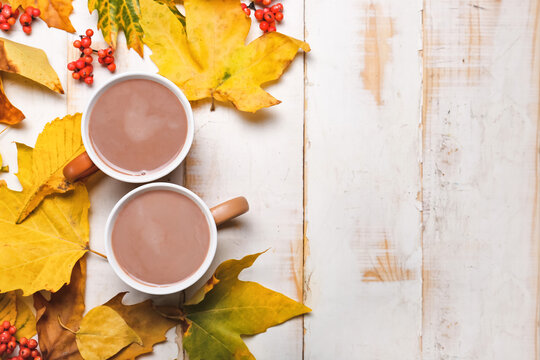 Cup of hot cacao drink with autumn leaves on white wooden background
