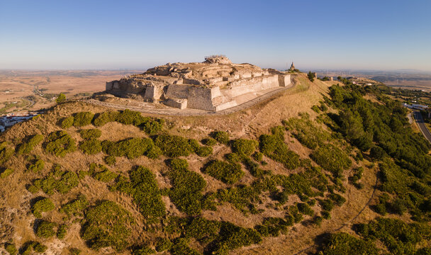 Aerial view of the castle of Medina-Sidonia in the early morning in sunshine. In the background you can see the church and behind it the Andalusian landscape. In the distance are wind turbines.