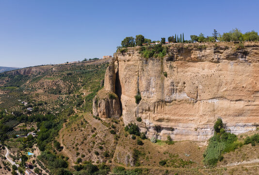 Aerial view of the high rock face of the Andalusian town of Ronda in sunshine and blue skies in summer. The rock on the left looks like a tower.