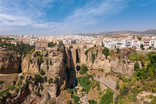 Impressive panoramic view from the air of the Andalusian city of Ronda with sunshine and blue skies in summer. In the middle the famous bridge with a waterfall.