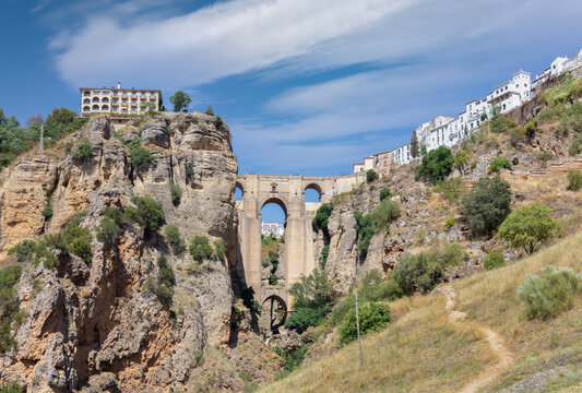 The famous arch bridge of Ronda in Andalusia in summer with a blue cloudy sky. The city is on top of the plateau. At the very bottom is a small waterfall.