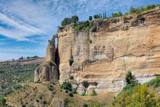 Summer view of the high rock face of the Andalusian city of Ronda in sunshine and a blue sky with clouds. The rock on the left looks like a tower.