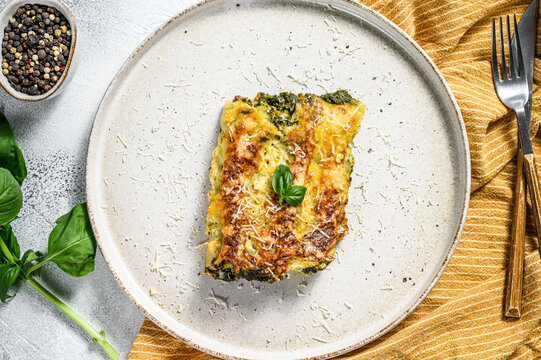 Cannelloni with ricotta and spinach. Italian cuisine. Gray background. top view