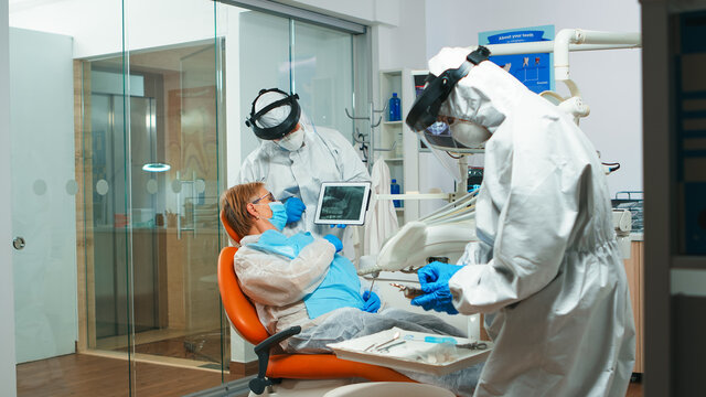 Dentist in protective equipment showing on tablet dental x-ray reviewing it with senior patient. Medical team wearing face shield coverall, mask, gloves, explaining radiography using notebook display