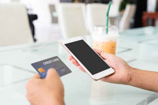 Hands of Asian woman using mobile phone with blank screen for copy space, advertisement while holding credit card in cafe. Close up. Technology and lifestyle concept.