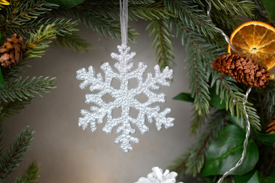Christmas decorations, close up of white snowflake on Christmas wreath.
