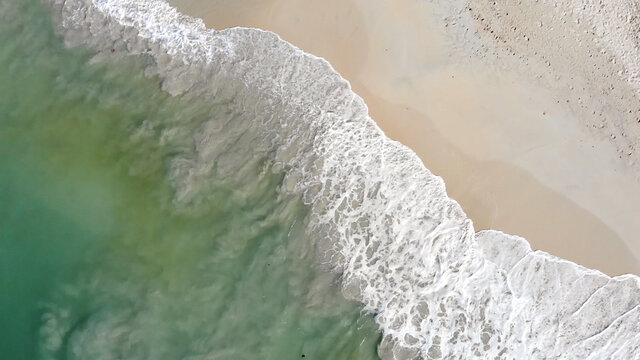 Relaxing aerial shot of waves washing the white sand beach in the carribean. White sand, clear water and crashing waves.