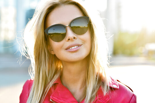 Outdoor fashion portrait of young pretty   blond woman in sunny day on street. Girl in sunglasses outdoor.