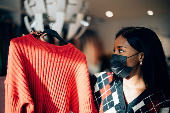 young woman with a black face mask standing in a fashion retail shop choosing a sweater