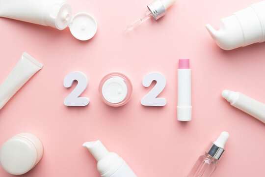 Best skincare products and cosmetic trends of 2021 concept. 2021 white number with lip balm, cream bottle, serum and lotion on pink background.