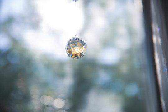 美しいガラスのクリスタルのサンキャッチャーの飾りがある窓辺