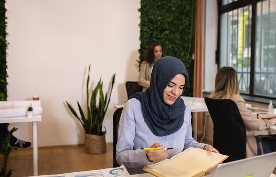 Portrait of a young muslim businesswoman working in an office while sitting at a table with colleagues in the background.