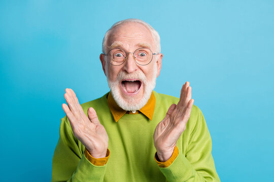 Photo of crazy retired granddad open mouth raise palms wear eyeglasses green pullover isolated blue color background