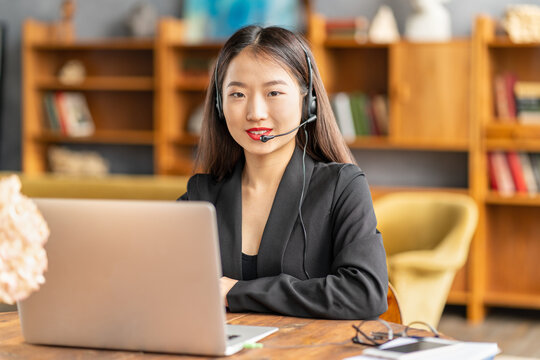 Happy asian businesswoman in headset speaking by conference call and video chat on laptop in office, smiling chinese support service agent consulting customer. Female portrait looking at camera