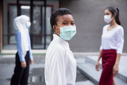 Happy smiling black African woman wearing face mask, observing new normal lifestyle of social distancing, keeping distance away from other people in public