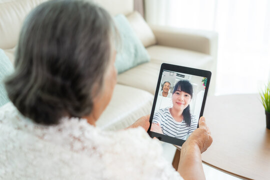 Asian elderly woman virtual happy hour meeting and talking online together with her daughter in video conference with tablet for a online meeting in video call for social distancing..