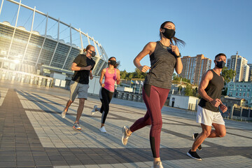 Young multi race sportive people in protective masks