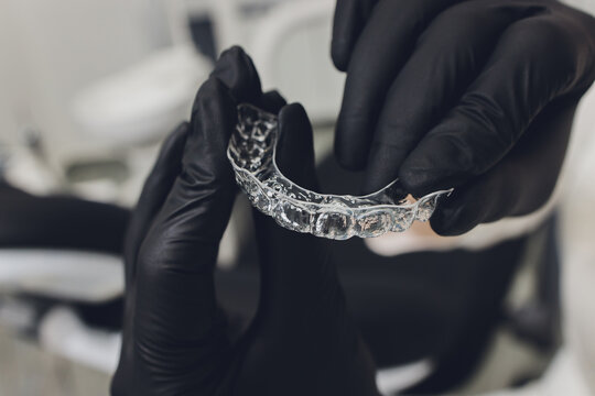 Close-up Of A Woman's Hand Putting Transparent Aligner In Teeth.