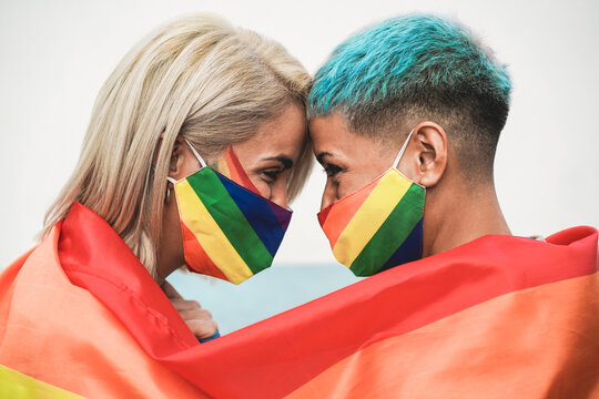 Young couple of women hugging under rainbow flag wearing colorful masks at gay pride event - Social distance, lgbt and love concept - Focus on ear