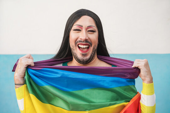 Happy drag queen wearing rainbow flag - Lgbt and transgender concept