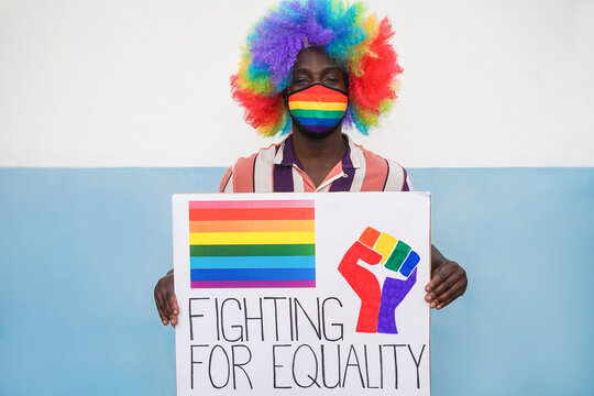 African man holding lgbt banner at gay pride demonstration while wearing rainbow safety mask - Equality right concept - Focus on face
