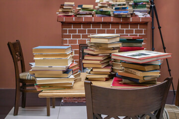 Library. Books in piles on a wooden table, next to the table is a wooden chair.