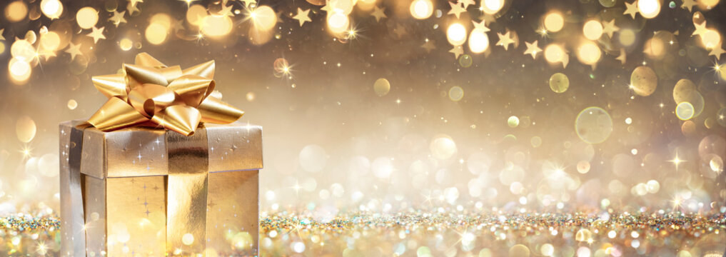 Golden Gift Box On Glitter In Abstract Background With Defocused Lights