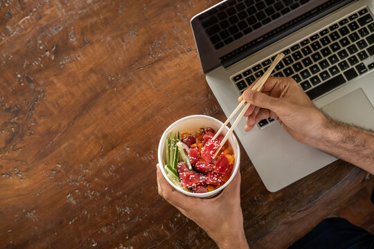 Busy young man in casual wear sitting at desk with a laptop at home or in the office and eating healthy takeout poke bowl food from container during lunch break. Healthy lifestyle concept. Top view