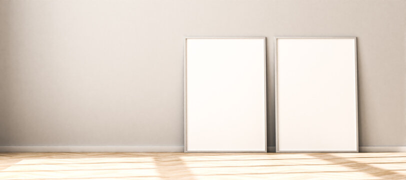 Two empty Picture Frames on parquet floor leaning against bright wall. Sunlight flooding in from the left - copy space to the left. 3d render mockup. Web banner size