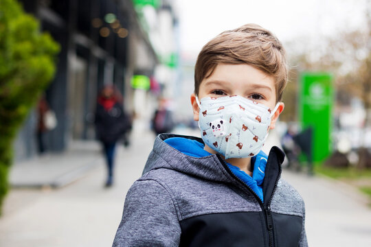 Smiling boy with kn95 face mask during corona virus in the city.