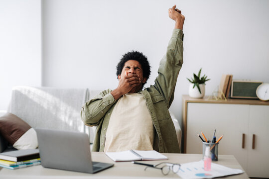Tired black student yawning and stretching during his remote studies from home