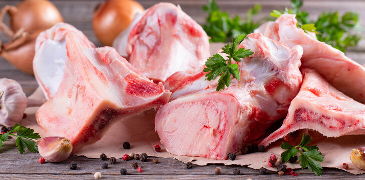 Raw beef bone for making broth on wooden background with vegetables and herbs. Banner
