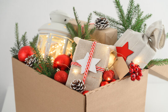Christmas gifts in eco-friendly reusable packaging and decorations in a cardboard box. Delivery and donation concept. Selective focus.