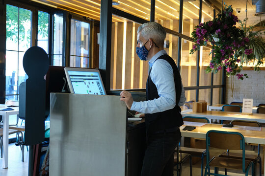 Waiter wearing face mask checking the tables on a counter touch screen. New normal in restaurants. Coronavirus pandemic.