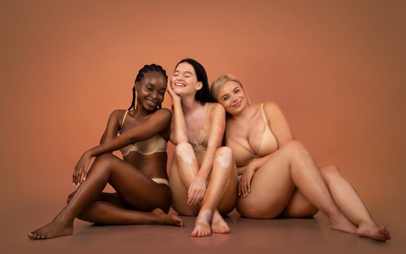Group of women with different body types and ethnicity sitting in underwear