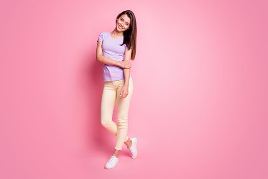 Full body photo of smiling friendly girl dressed purple t-shirt yellow pants sneakers isolated on pink color background
