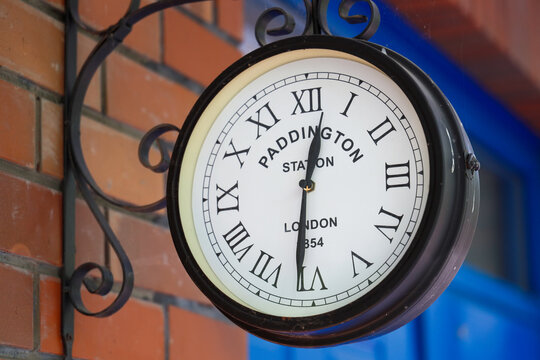 English brick house corner with retro clock with Paddington Station London text on it.