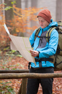 Young hiker looking at a map in a colorful forest in fall