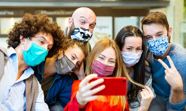 smiling group of people wearing protective face mask posing for a picture together in front of a smartphone.happy social influencers taking a selfie pic together.concept about new normal lifestyle