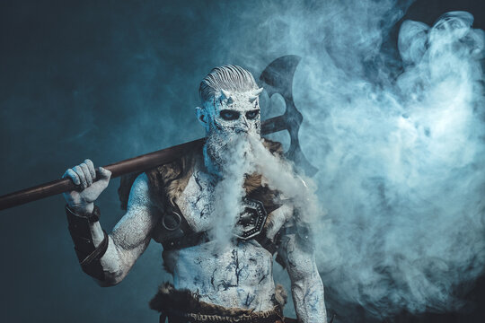 Nordic undead in dark armour with fur and naked torso with cold breath and huge axe on his shoulder in frosty fog.