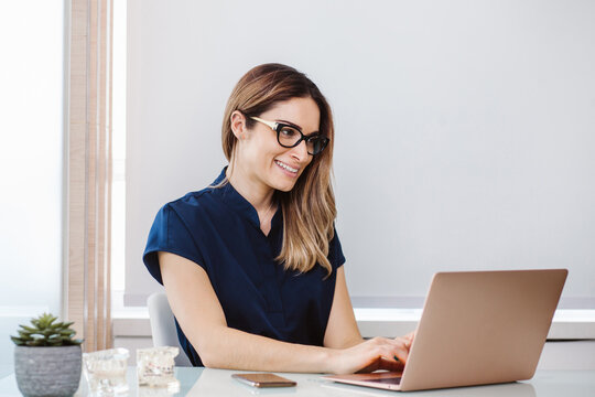 Latin doctor woman working on the computer on her desk