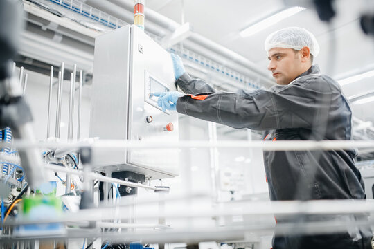 Factory engineer man operating machine control panel in dairy milk production plant