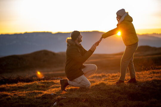 Silhouettes of a man making a marriage proposal to his girlfriend on the mountain peak at sunset. Landscape with the silhouette of lovers against the colorful sky.
