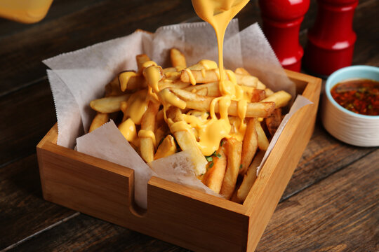 Man pouring melted cheese sauce on French fries in a wooden box
