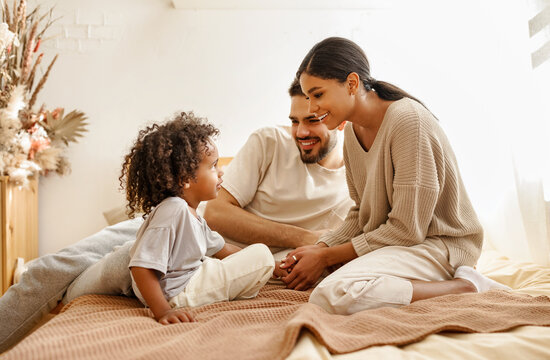 happy multi ethnic family mom, dad and child  laughing, playing and tickles   in bed   at home.