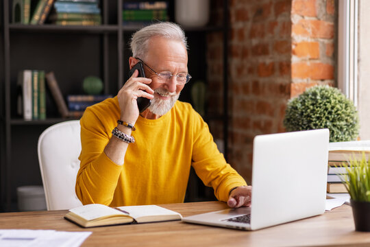 Cheerful aged freelancer making call in home office.