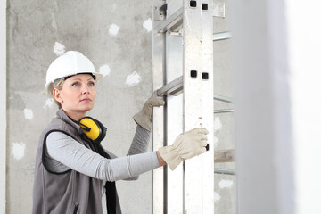 woman construction worker builder portrait wearing white helmet and hearing protection headphones, holding a ladder on interior site building background with scaffolding Wall mural