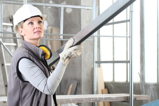 woman construction worker builder portrait wearing white helmet and hearing protection headphones, holding a metal stud for drywall on interior site building background with scaffolding